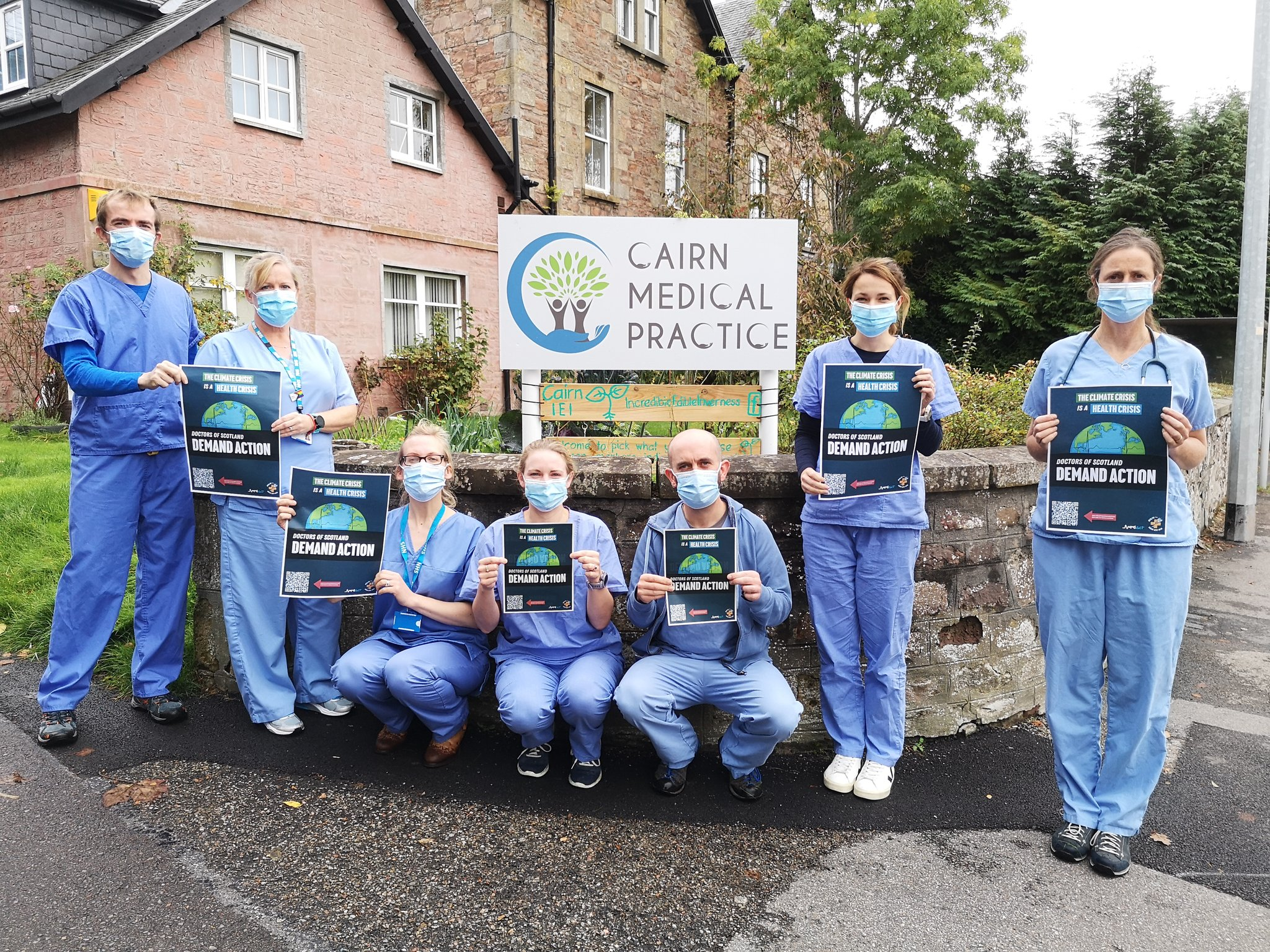 Collection of Scottish Doctors in scrubs holding posters